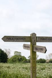 an old wooden signpost in a field